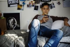 Adolescente que usa smartphone en concepto social del dormitorio un medios Imágenes de archivo libres de regalías