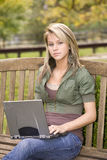 Adolescente que usa su computadora portátil en el parque Foto de archivo