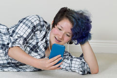 Adolescente que usa su teléfono celular y escuchando la música en casa Foto de archivo libre de regalías