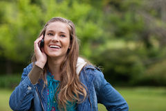 Adolescente que usa su teléfono móvil mientras que sonríe Fotografía de archivo libre de regalías
