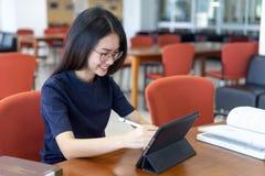 Adolescente que usa a tabuleta digital na sala de aula fotografia de stock