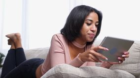 Adolescente que usa a tabuleta digital no sofá vídeos de arquivo