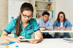 Adolescente que usa a tabuleta na sala de aula moderna Imagem de Stock Royalty Free