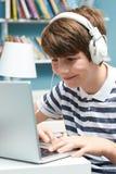Adolescente que usa tecnología en dormitorio Fotos de archivo libres de regalías