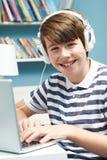 Adolescente que usa tecnología en dormitorio Fotografía de archivo libre de regalías