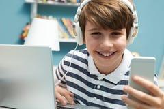 Adolescente que usa tecnología en dormitorio Fotos de archivo