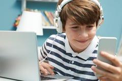 Adolescente que usa tecnología en dormitorio Imagen de archivo libre de regalías