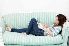 Adolescente que usa um portátil Fotos de Stock Royalty Free
