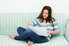 Adolescente que usa un ordenador portátil Imágenes de archivo libres de regalías