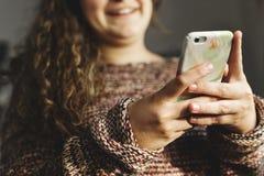 Adolescente que usa un smartphone en un concepto social de los medios y del apego de la cama Imágenes de archivo libres de regalías