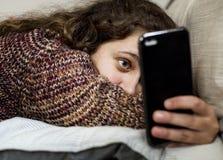 Adolescente que usa un smartphone en un concepto social de los medios y del apego de la cama foto de archivo