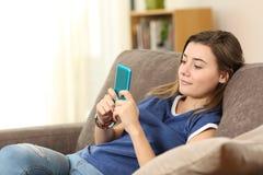 Adolescente que usa un teléfono elegante azul en casa Foto de archivo