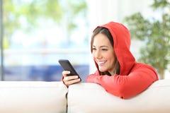 Adolescente que usa un teléfono elegante en casa Imagenes de archivo