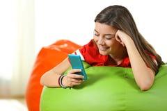 Adolescente que usa un teléfono elegante en un taburete colorido Fotografía de archivo