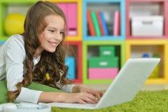 Adolescente que usa una computadora portátil Foto de archivo libre de regalías