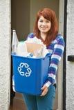 Adolescente que vacia el reciclaje en casa Foto de archivo