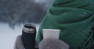 Adolescente que vierte el cacao caliente en la taza de papel en parque en un día de invierno Imágenes de archivo libres de regalías