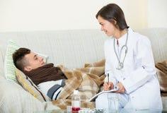 Adolescente que visita del doctor con frío en casa Foto de archivo libre de regalías