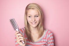 Adolescente quién que cepilla su pelo en su dormitorio Foto de archivo libre de regalías