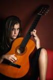 Adolescente rebelde que sostiene una guitarra acústica Foto de archivo libre de regalías