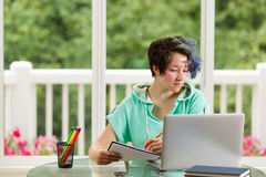 Adolescente relajado que hace su trabajo de la escuela en casa Fotos de archivo libres de regalías