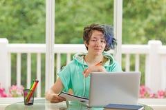Adolescente relajado que trabaja en sus estudios mientras que en casa Imágenes de archivo libres de regalías