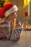 Adolescente réfléchie dans le chapeau de Santa avec le journal intime dans la cuisine Images stock