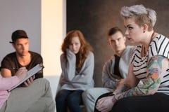 Adolescente ribelle tatuato che si siede davanti ad un terapista che fotografie stock libere da diritti