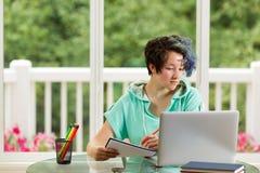 Adolescente rilassato che fa il suo lavoro della scuola a casa Fotografie Stock Libere da Diritti