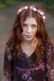 Adolescente rizado hermoso en una guirnalda de flores Imagenes de archivo