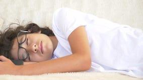 Adolescente rizado lindo que duerme en el sofá con el teléfono a disposición Falta de sue?o Primer, 4K metrajes