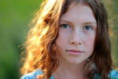 Adolescente rizado que mira la cámara en luz del sol Imagen de archivo libre de regalías