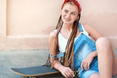 Adolescente rojo del pelo con las pecas en estilo sport con el monopatín en día de verano en la calle imagenes de archivo