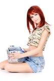 Adolescente rojo del pelo que celebra al lector de cd Fotografía de archivo