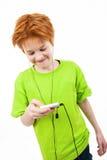 Adolescente rojo escucha la música Fotografía de archivo