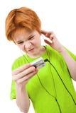 Adolescente rojo escucha la música Fotos de archivo