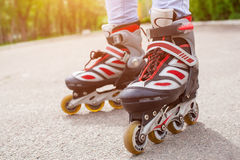 Adolescente rollerblading en el asfalto en el parque, piernas de la muchacha Foto de archivo