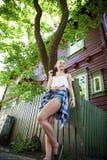 Adolescente rubio atractivo y casa de madera Foto de archivo