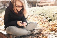 Adolescente rubio caucásico en vaqueros con el teléfono móvil Imagenes de archivo