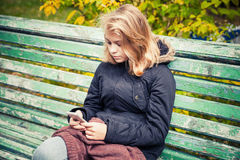 Adolescente rubio caucásico hermoso con el teléfono Imagen de archivo libre de regalías
