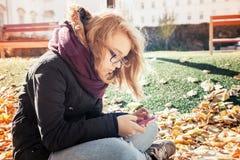 Adolescente rubio caucásico lindo con el teléfono celular Fotos de archivo libres de regalías