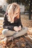 Adolescente rubio caucásico lindo con el teléfono elegante Imágenes de archivo libres de regalías