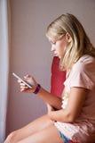 Adolescente rubio caucásico lindo que usa smartphone Foto de archivo libre de regalías