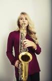 Adolescente rubio con el saxofón Fotografía de archivo