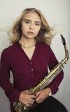 Adolescente rubio con el saxofón Imagenes de archivo