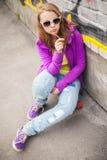 Adolescente rubio con la piruleta, retrato urbano vertical Imagenes de archivo