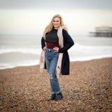 Adolescente rubio confiado solamente en una playa fría Foto de archivo