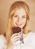Adolescente rubio de la belleza joven que come el chocolate Fotografía de archivo libre de regalías