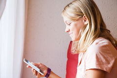 Adolescente rubio de risa lindo con el teléfono celular Foto de archivo libre de regalías