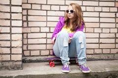 Adolescente rubio en gafas de sol con el monopatín Foto de archivo libre de regalías